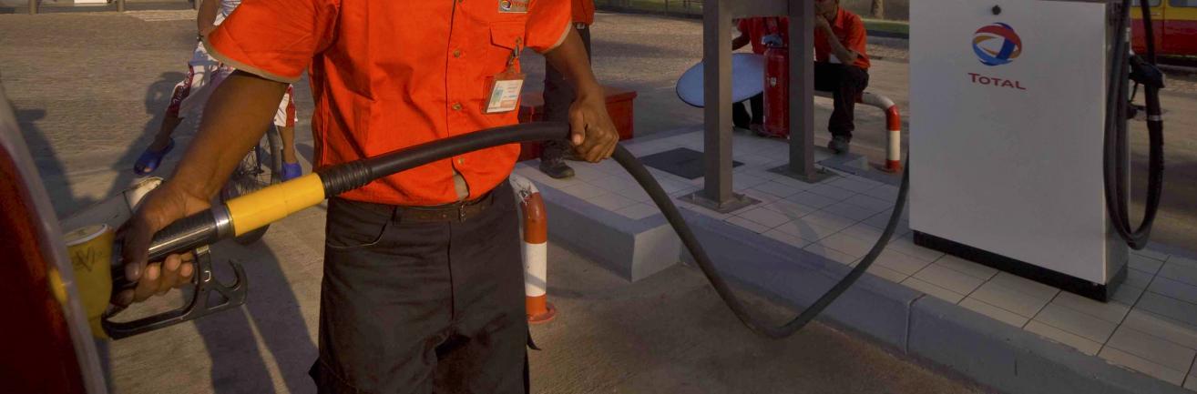 À la station-service Morondava, un pompiste fait le plein de la voiture d'un client.