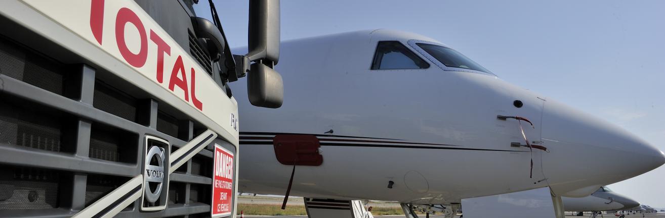 Gros plan sur l'avant d'un camion avitailleur Total sur l'aéroport de Nice-Côte d'Azur. A l'arrière plan, un jet.